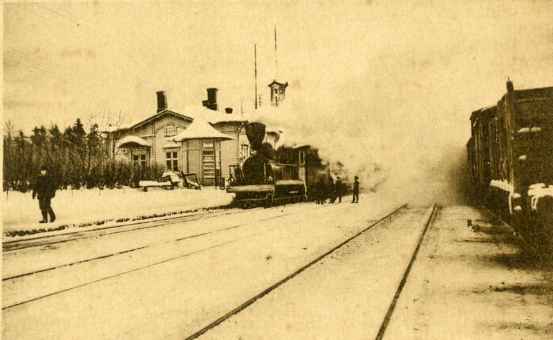Lumisia raiteita, joista vasemmalla reunimmaisella seisoo höyryveturin vetämä juna. Veturin piipusta tupruaa sankasti höyryä. Taustalla on asema, jonka katolla on lunta. Veturin luona ja asemalaiturilla on ihmisiä.