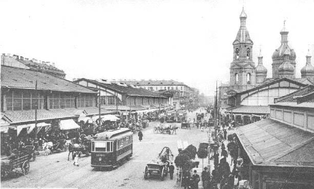 Leveä katu, jonka molemmilla puolilla on rakennuksia. Kadulla on paljon ihmisiä, hevoskärryjä ja raitiovaunut ajavat katua pitkin. Taustalla oikealla on kirkko.