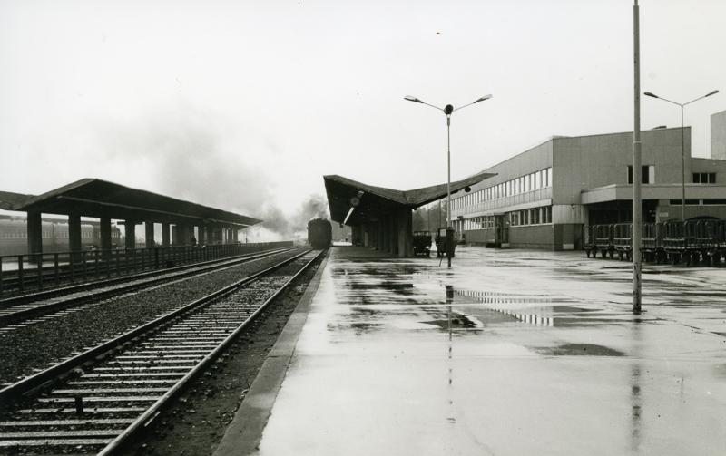 Rataa, laituria, laiturikatosta ja taustalla Kouvolan asema sekä poistuva juna.